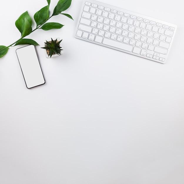 Kantoorbehoeftenregeling op witte achtergrond met telefoonmodel Gratis Foto
