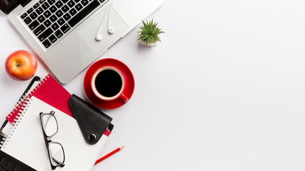 Kantoorbenodigdheden, oogglazen, appel, laptop, oortelefoons en cactusinstallatie op bureau Premium Foto