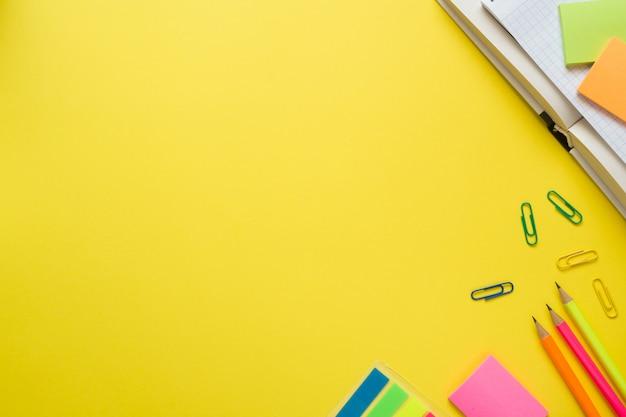 Kantoorbenodigdheden op gele tafel met kopie ruimte. Premium Foto