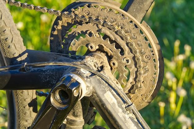 Kapotte fiets die moet worden gerepareerd terwijl hij op het groene gras ligt terwijl zijn pedalen worden verwijderd. Premium Foto