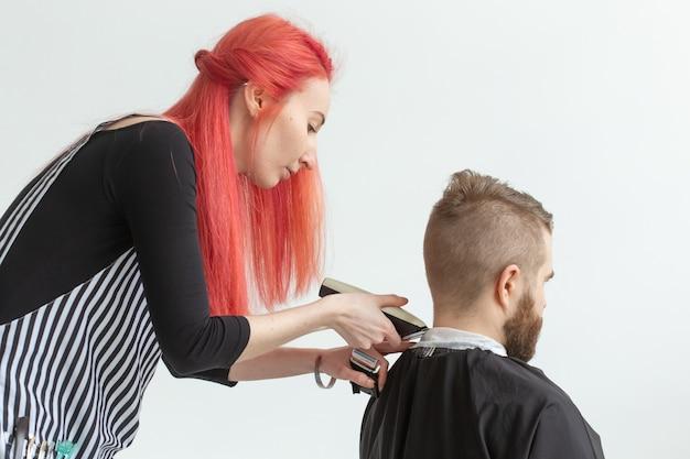 Kapper, haarstylist en kapper winkelconcept - vrouw haarstylist snijden een bebaarde man Premium Foto