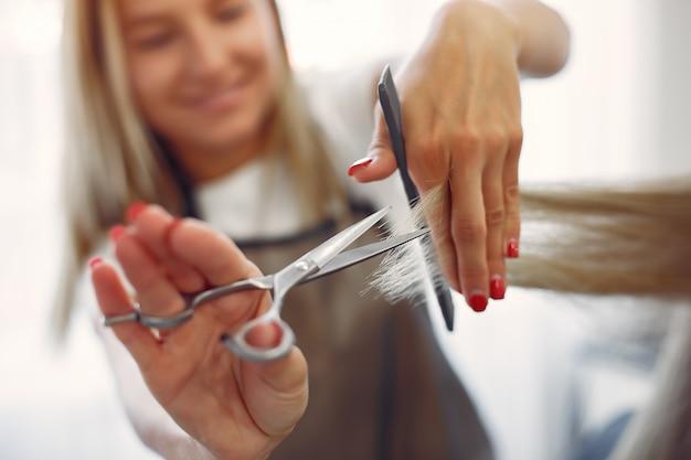 Kapper knippen haar haar cliënt in een kapsalon Gratis Foto