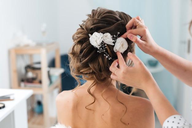 Kapper maakt een elegante kapselstylende bruid met witte bloemen in haar haar Premium Foto