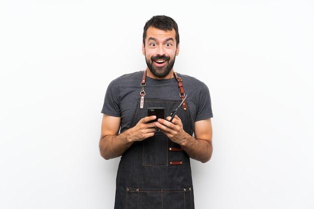 Kapper man in een schort verrast en een bericht verzenden Premium Foto