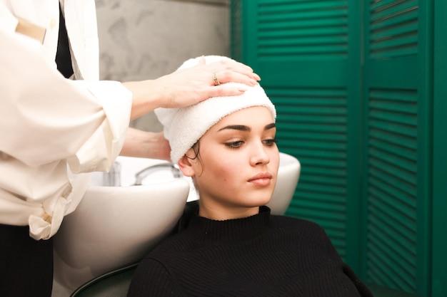 Kapper wikkelt het haar van de klant in een handdoek na het wassen van het hoofd Premium Foto