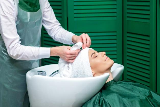 Kapper wikkelt het haar van de klant in een handdoek. Premium Foto