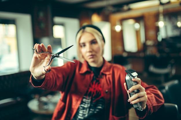 Kapperszaak. vrouwelijke kapper bij salon. geslachtsgelijkheid. vrouw in het mannelijke beroep. handen sluiten omhoog Gratis Foto
