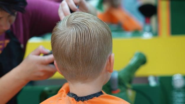 Kapsel van een kleine jongen in een kinderkapsalon Premium Foto