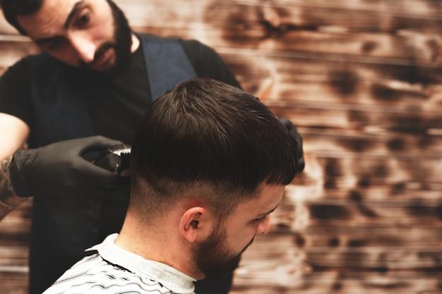 Kapselhoofd in herenkapper. kapper knipt het haar op het hoofd van de cliënt. het proces van het creëren van kapsels voor mannen. kapperszaak. selectieve aandacht. Premium Foto