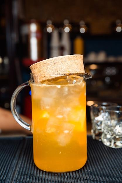 Karaf met sinaasappelsap en ijsblokjes. Premium Foto
