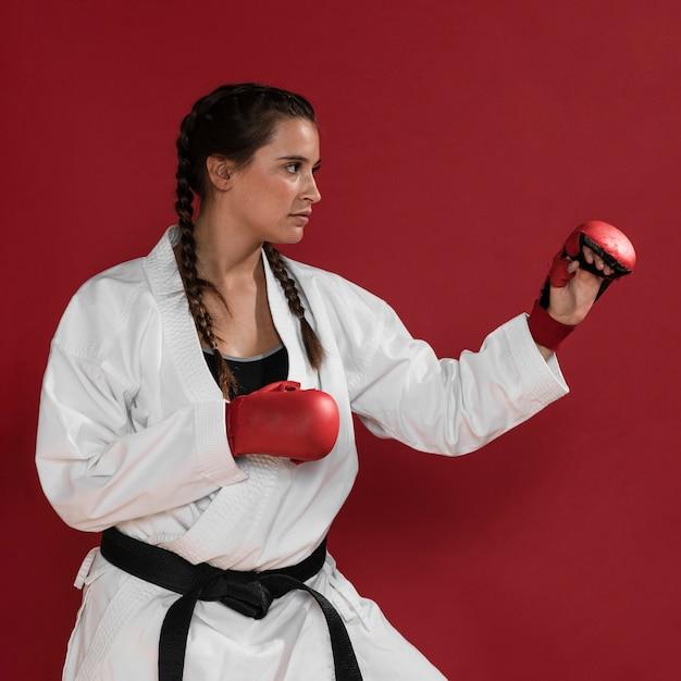 Karatevrouw in actie op rode achtergrond wordt geïsoleerd die Gratis Foto
