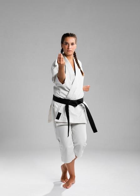Karatevrouw in actie op witte achtergrond wordt geïsoleerd die Gratis Foto