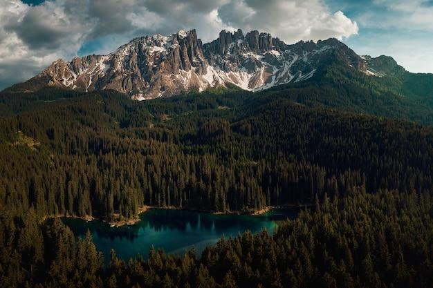 Karersee omgeven door bossen en dolomieten onder een bewolkte hemel in italië Gratis Foto