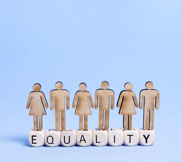 Kartonmensen die zich op die gelijkheidswoord bevinden op houten kubussen wordt geschreven Gratis Foto