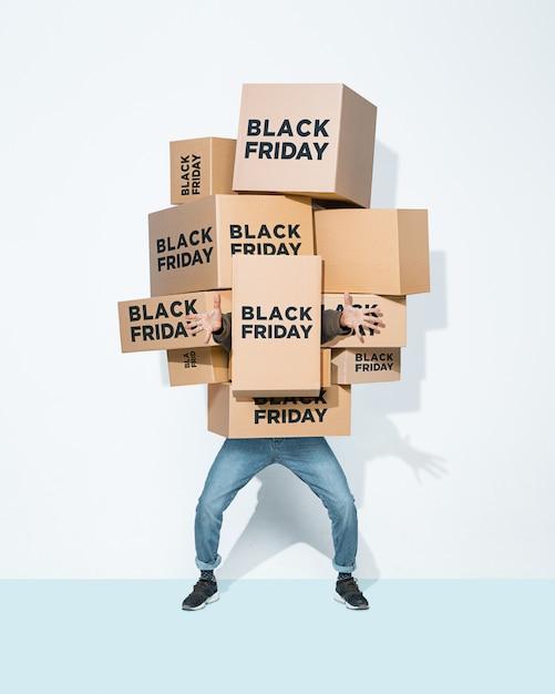 Kartonnen dozen met black friday inscriptie in de handen van een jonge man Gratis Foto