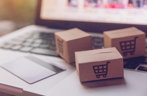Kartonnen dozen met een winkelwagen logo en creditcard op een laptop toetsenbord. Premium Foto
