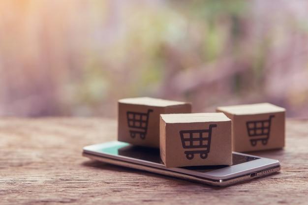 Kartonnen dozen met een winkelwagen logo en smartphone op houten tafelblad. Premium Foto