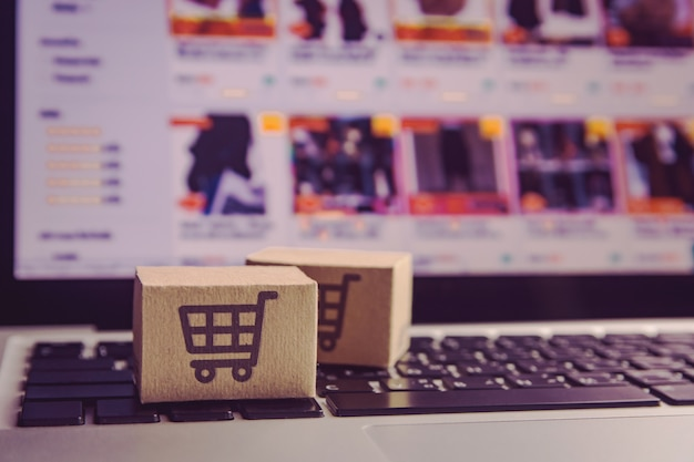 Kartonnen dozen met een winkelwagen-logo op een laptop toetsenbord Premium Foto