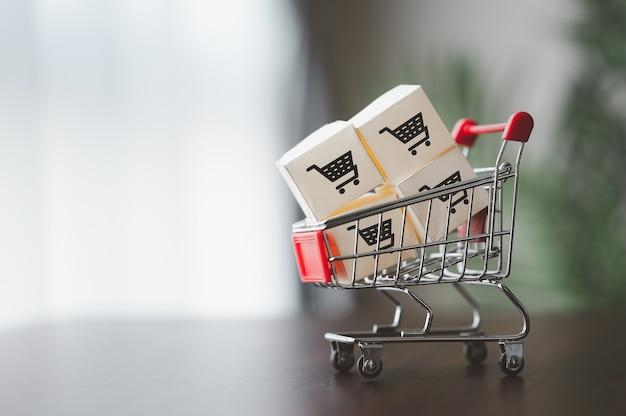 Kartonnen dozen met winkelwagenlogo in een trolley voor bezorging. online winkelen of marketing en commerce concept Premium Foto