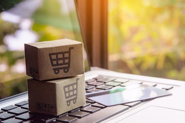Kartonnen dozen of pakjes met een winkelwagentje en een creditcard op een laptoptoetsenbord. Premium Foto