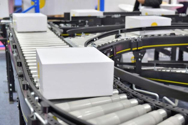 Kartonnen dozen op transportband in distributie magazijn. pakketten transport systeemconcept. Premium Foto