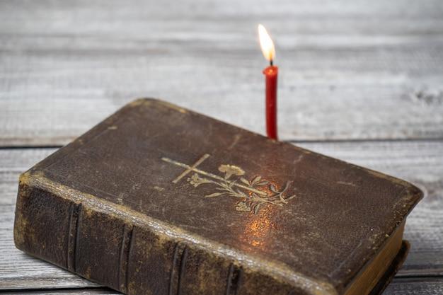 Katholieke bijbel en rode kerk brandende kaars op houten achtergrond Premium Foto