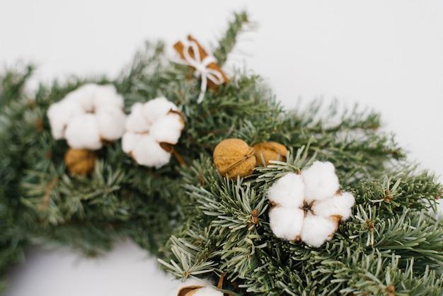 Katoenen bloem en okkernoten in kerstmiskroon, close-up van kroon Premium Foto