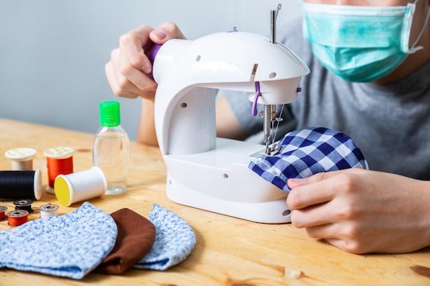 Katoenen het vrouwen naaiende doek gezichtsmasker om thuis tegen het coronavirus te beschermen. zelfgemaakt handwerk beschermend masker tegen covid 19 virus. herbruikbaar gezichtsmasker. Premium Foto