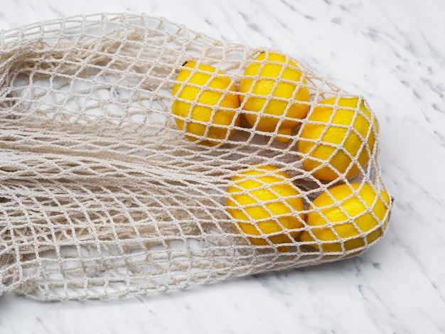 Katoenen tas met hoge hoek en citroenen Gratis Foto