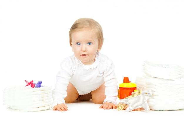Kaukasisch jong geitje met gestapelde luiers en speelgoed dat op witte achtergrond wordt geïsoleerd Premium Foto