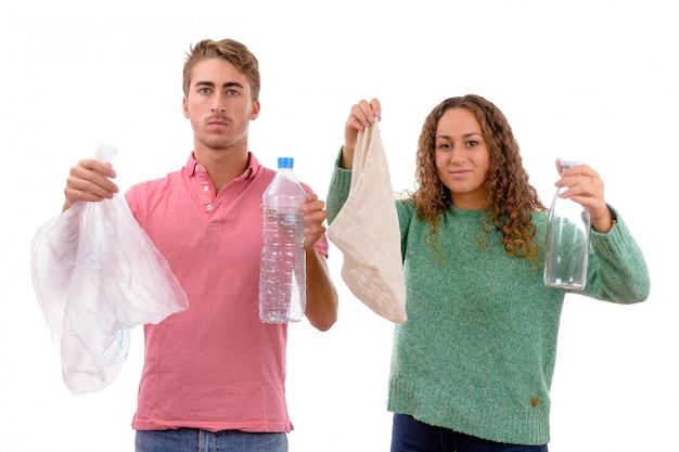 Kaukasisch jong jongen en meisje met een te hergebruiken stoffenzak en glazen fles en plastic zak en fles aan geïsoleerd recycling Premium Foto