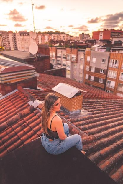 Kaukasisch jong meisje dat van zonsondergang met roofview geniet over donostia-san sebastian, baskenland. Premium Foto
