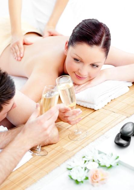 Kaukasisch jong paar dat van een achtermassage geniet en champagne drinkt Premium Foto