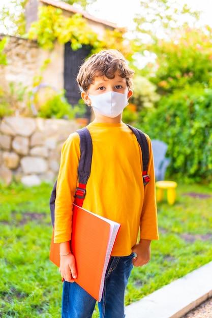 Kaukasisch kind met gezichtsmasker klaar voor terug naar school. nieuwe normaliteit, sociale afstand, coronavirus-pandemie, covid-19. oranje t-shirt, rugzak en een notitieblok in de hand Premium Foto