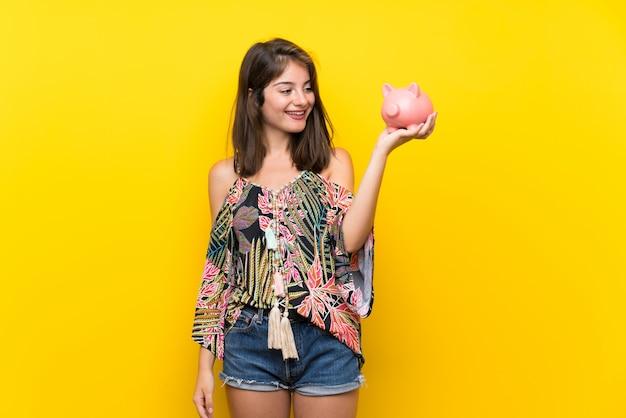 Kaukasisch meisje dat in kleurrijke kleding een grote spaarpot houdt Premium Foto