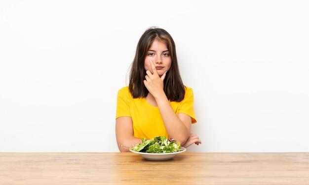 Kaukasisch meisje dat met salade een idee denkt Premium Foto