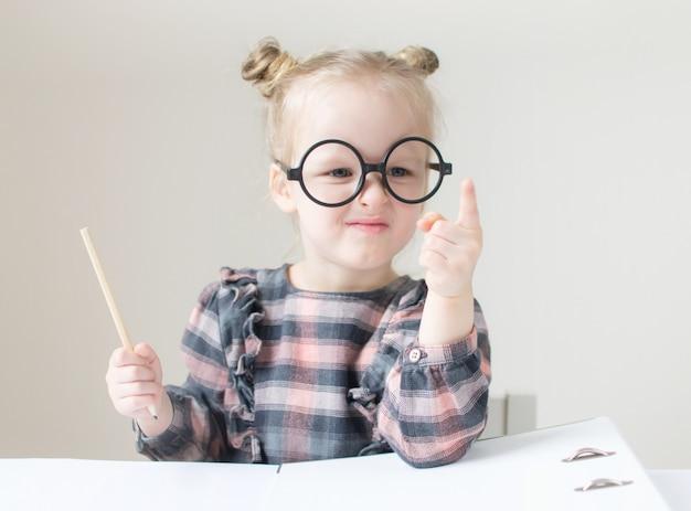 Kaukasisch meisje met ronde glazen. kleine leraar. grappige bril humor. retro stijl Premium Foto