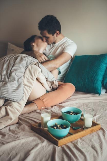 Kaukasisch paar kussen en omhelzen in bed voordat ze granen met melk eten Premium Foto