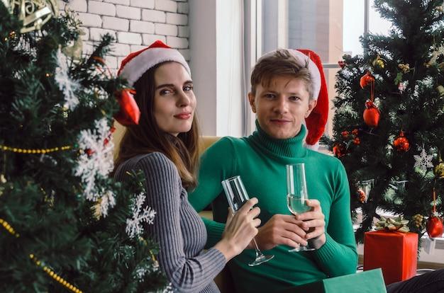 Kaukasisch zoet paar met rode kerstmuts geniet van het drinken van champagne en kijken naar camera met kerstboom vieren binnenshuis Premium Foto