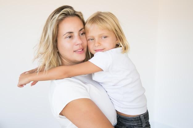 Kaukasische aantrekkelijke moeder die dochter houdt en weg kijkt Gratis Foto