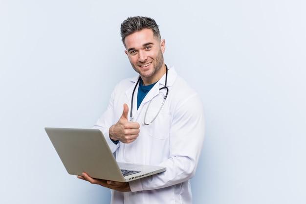 Kaukasische artsenmens die laptop houdt glimlachend en duim opheft Premium Foto
