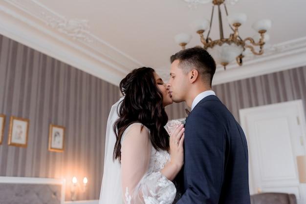 Kaukasische bruid en bruidegom kussen teder in de lichte hotelkamer Gratis Foto