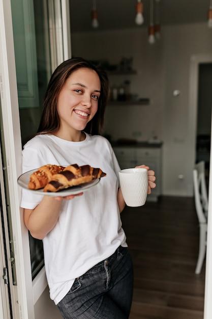Kaukasische glimlachende vrouw die wit t-shirt met donker haar en een gezonde huid draagt die ochtendkoffie en croissants voor ontbijt thuis houdt. Gratis Foto