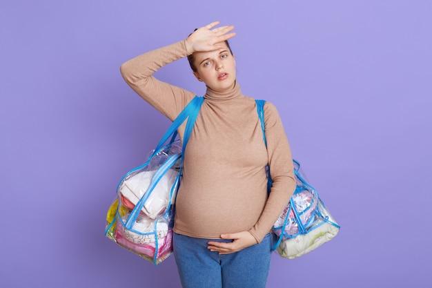 Kaukasische jonge mooie zwangere, vermoeide toekomstige moeder die vermoeidheid en hoofdpijn voelt, ziet er moe en uitgeput uit, raakt haar voorhoofd aan, houdt twee tassen vast, gaat naar het kraamhuis. Gratis Foto