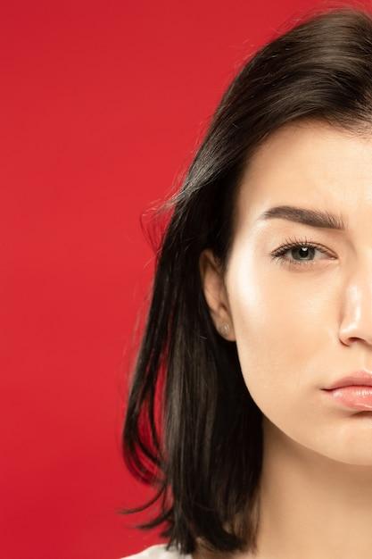 Kaukasische jonge vrouw close-up portret op rode studio Gratis Foto