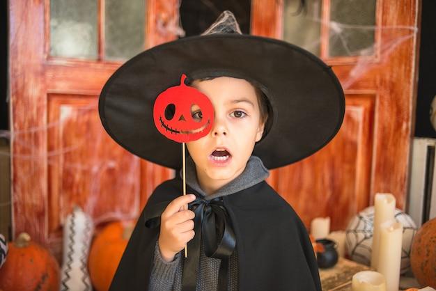 Kaukasische jongen in carnaval-tovenaarskostuum met document pompoen op halloween-decorachtergrond Premium Foto