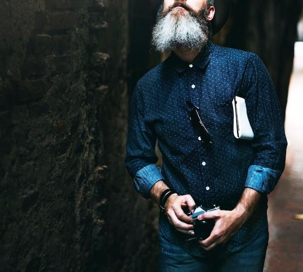 Kaukasische mens die met filmcamera loopt in straatsteeg Gratis Foto