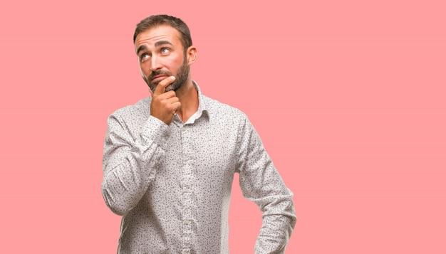 Kaukasische mens die op grijze brackground over een idee denkt Premium Foto