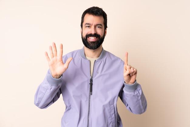 Kaukasische mens met baard die een jasje over geïsoleerde muur draagt die zes met vingers telt Premium Foto