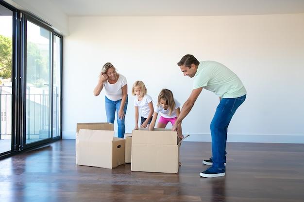 Kaukasische ouders kartonnen dozen met dochters uitpakken in lege ruimte met balkon Gratis Foto